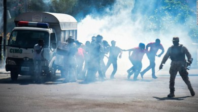 People run from tear gas as police disperse demonstrators near the National Palace in Port-au-Prince on Wednesday.