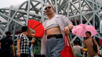 A man sports a so-called Beijing bikini as he fishes by Houhai Lake in Beijing on July 1, 2019.