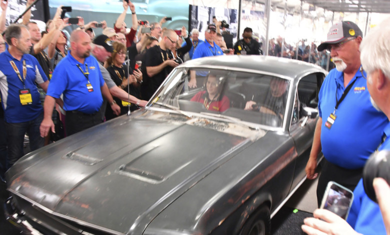 """People surround the original 1968  """"Bullitt"""" Mustang GT Friday, Jan. 10, 2020 in Kissimmee, Fla. The iconic Highland Green 1968 Mustang GT that once made history for its appearance in the film """"Bullitt"""" is now making history again. It fetched $3.74 million Friday at Mecum's Kissimmee auction, making it the most expensive Mustang ever sold. (Malcolm Denemark/Florida Today via AP)"""