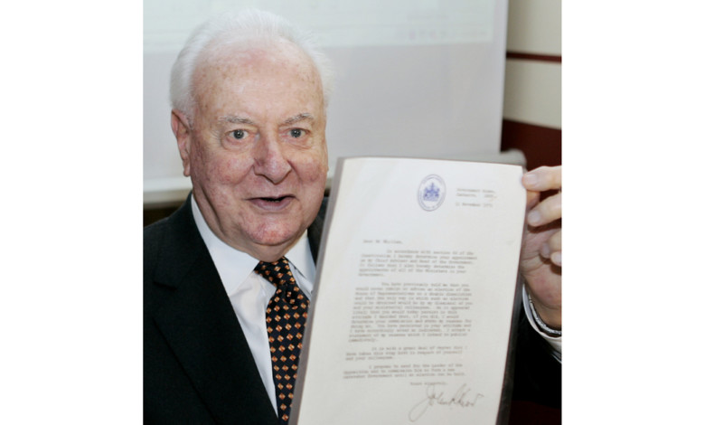 FILE – In this Nov. 7, 2005, file photo, former Australian Prime Minister Gough Whitlam holds up the original copy of his dismissal letter he received from then Governor-General Sir John Kerr on Nov. 11, 1975, at a book launch in Sydney, Australia. The High Court's majority decision in historian Jenny Hocking's appeal on Friday, May 29, 2020 overturned lower court rulings that more than 200 letters between the monarch of Britain and Australia and Governor-General Sir John Kerr before he dismissed Prime Minister Gough Whitlam's government were personal and might never be made public. (AP Photo/Mark Baker, File)