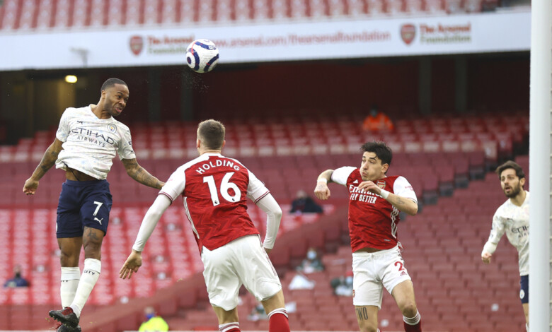 Manchester City's Raheem Sterling, left, scores his side's opening goal during the English Premier League soccer match between Arsenal and Manchester City at the Emirates stadium in London, England, Sunday, Feb. 21, 2021. (Julian Finney/Pool via AP)