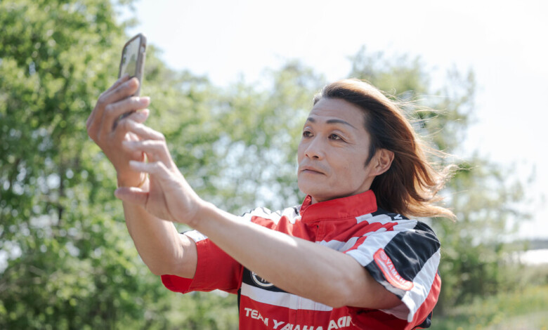 Yasuo Nakajima takes a selfie in Ibaraki prefecture, Japan, on May 1. The 50-year-old used an app to transform himself into a young, pretty female motorcycle enthusiast. (Irwin Wong for The Washington Post)