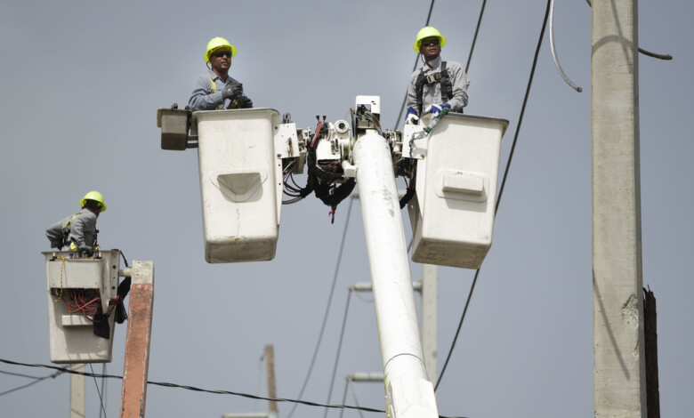 FILE – In this Oct. 19, 2017 file photo, Puerto Rico Electric Power Authority workers repair distribution lines damaged by Hurricane Maria in the Cantera community of San Juan, Puerto Rico. Luma, the private company that took over power transmission and distribution in June 2021 has struggled with widespread outages, affecting more than 1 million customers so far in its first two weeks, triggering several mayors to declare a state of emergency and distribute ice and generators.(AP Photo/Carlos Giusti, File)